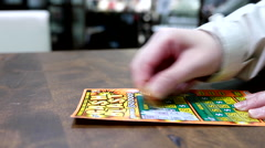 Close up woman scratching lottery ticket called cash blast inside shopping mall Stock Footage