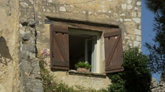 Window with wooden shutters and a flower pot in Saint-Paul-de-Vence - stock footage