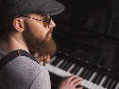 Talented bearded musician is playing the piano Stock Photos