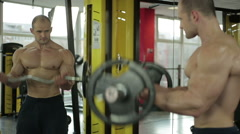 Self-confident bodybuilder looking in the mirror while exercising with barbell - stock footage