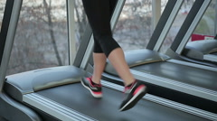 Feet of young sportive woman running fast on treadmill, training for wellness - stock footage