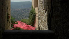 Tilt up of the red umbrellas seen from a sloped street, Saint-Paul-de-Vence Stock Footage