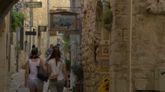 People walking on Rue Grande, visiting the art galleries in Saint-Paul-de-Vence Stock Footage