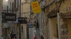 Tourists visiting the galleries and stores on Rue Grande, Saint-Paul-de-Vence Stock Footage