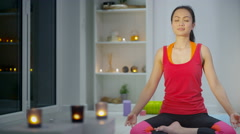 4K Young woman relaxing & meditating at home with many lit candles Stock Footage