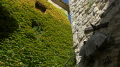 Iron brackets hold the carved sign Les Quatre Coins in Saint-Paul-de-Vence Stock Footage