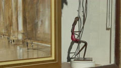 Woman in a swing sculpture next to a painting in Saint-Paul-de-Vence Stock Footage