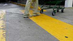 Close up woman pushing shopping cart walking on the yellow sidewalk Stock Footage