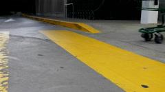 Close up woman pushing shopping cart walking on the yellow sidewalk - stock footage