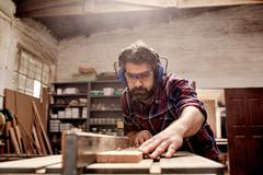 Carpentry business owner cutting a plank of wood in workshop - stock photo