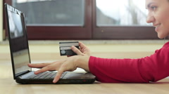 Young woman lying on floor with laptop computer and credit card HD Stock Footage