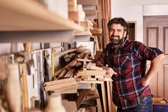 Carpentry business owner standing smiling in his workshop Stock Photos