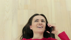 Portrait of a happy woman lying on floor and talking on the phone, top viewHD Stock Footage