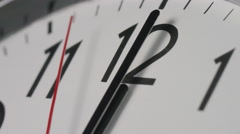 Slow zoom in to a clock face as the clock strikes midnight, or midday - stock footage