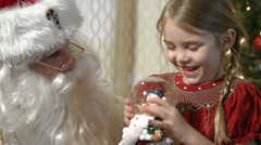 Christmas Eve Visit from Santa Claus - Little girl shaking snow globe - stock footage