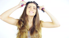 Happy beautiful woman brushing long amazing hair with 4 brushes Stock Footage