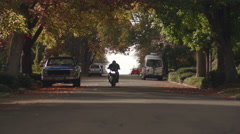 Man Riding Fast Motorcycle in City Streets Toward Camera in Fall Season - stock footage