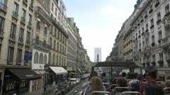 Sightseeing tour bus on Paris street with Parisian skyline behind. - stock footage