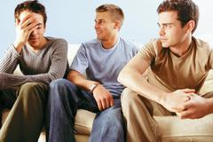 Men joking around on sofa Stock Photos