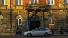 People walking and cars driving in front of a polyclinic on a street in Zagreb Stock Footage