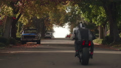 Man Riding Motorcycle Away from Camera in City Streets during Fall Season - stock footage