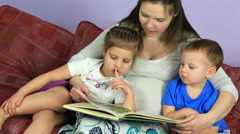 Mom reading a book to their little children. Happy family waiting for third - stock footage