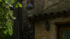 Stock Video Footage of Tilt up of the old buildings with street lamps and antennas, Saint-Paul-de-Vence