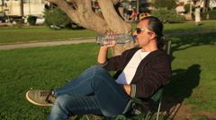 Tired man drinking water and reading book in park Stock Footage