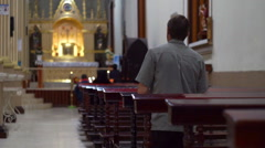 Man Kneels on Church Pew and Prays - stock footage