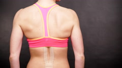 Woman with medical kinesio taping on back doing exercise 4K Stock Footage