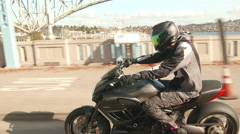 Man Riding Motorcycle in City Speeding Across Bridge with Water in Background Stock Footage