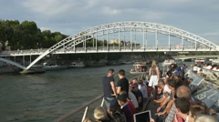 Sightseeing tour boat on Paris rive Seine with Parisian skyline Stock Footage
