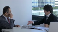 Japanese businesspeople discussing in a modern office Stock Footage