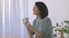 Senior Japanese woman having coffee in the living room Stock Footage
