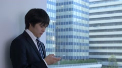 Young Japanese businessman with smartphone in a modern office Stock Footage