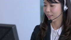 Young Japanese woman working at a call center in a modern office Stock Footage