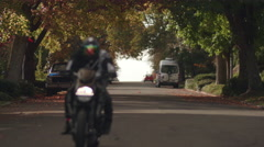 Man Riding Motorcycle in City Streets Toward Camera in Fall Season - stock footage