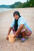 Musilim woman collecting shells on a beach. Stock Photos