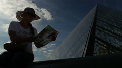 Girl looking at a map next to Palais du Louvre Stock Footage