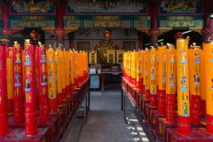 Giant Red and Gold Candles Lighted on an Altar chinese temple shrine Stock Photos