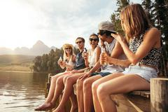 Friends sitting on pier at lake drinking beers - stock photo
