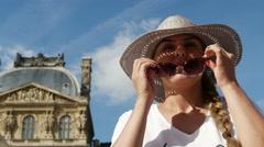 Beautiful woman visiting Paris. Girl sitting next to Pyramide du Louvre Stock Footage