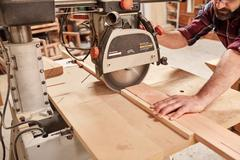 Radial arm circular saw cutting through wooden plank - stock photo