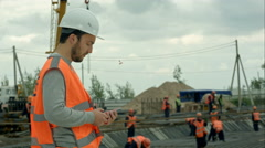 Construction worker talking on the phone at a building site Stock Footage