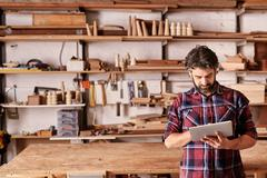 Artisan carpenter in his woodwork studio using digital tablet - stock photo