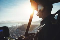 Helicopter pilot flying aircraft over a city - stock photo