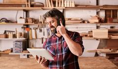 Man with beard in woodwork studio using phone and tablet - stock photo