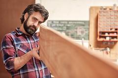 Craftsman in his workshop looking down length of wooden plank Stock Photos