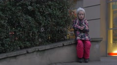 Bored Kid Girl is Sitting on a Parapet Little Child Plays Outdoors Blonde Kid Stock Footage