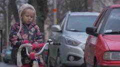 Kid Unties Her Scarf Going to Ride a Bicycle City Street Cars Are Parked Along Stock Footage